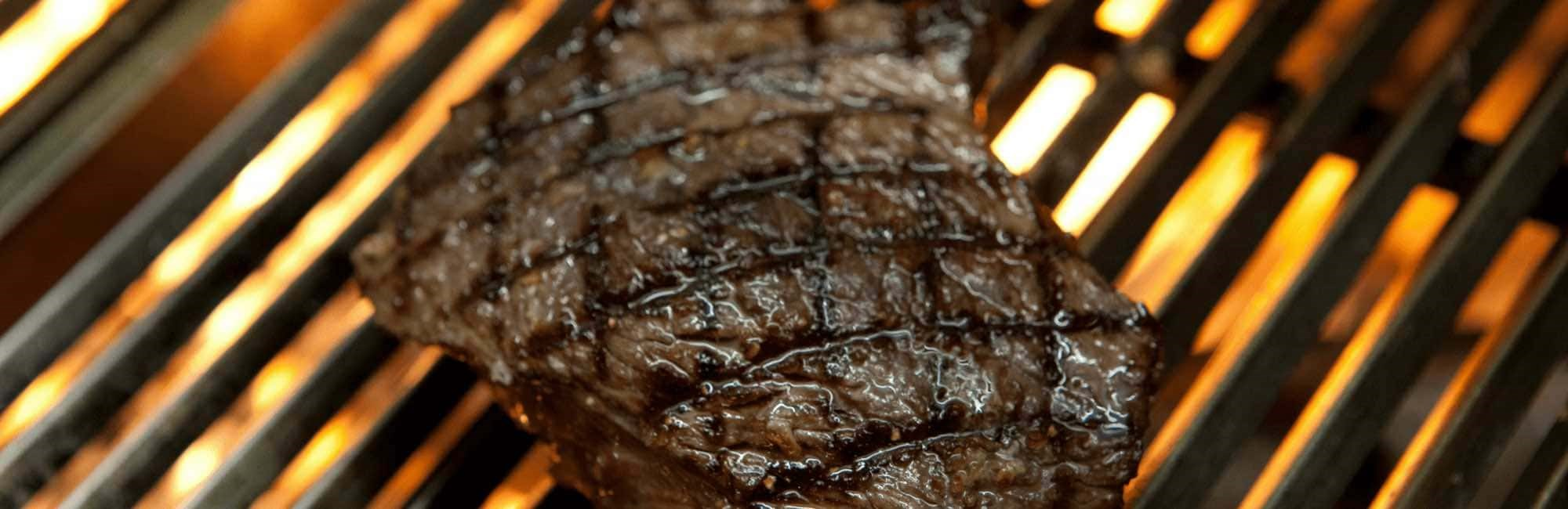 Large cut of beef cooking on the bespoke Argentinian grill
